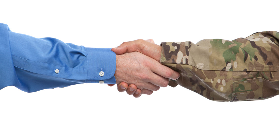 A businessman and a man in military uniform shaking hands.