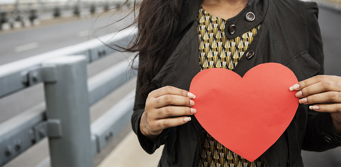 A woman holding a paper heart in front of her chest.